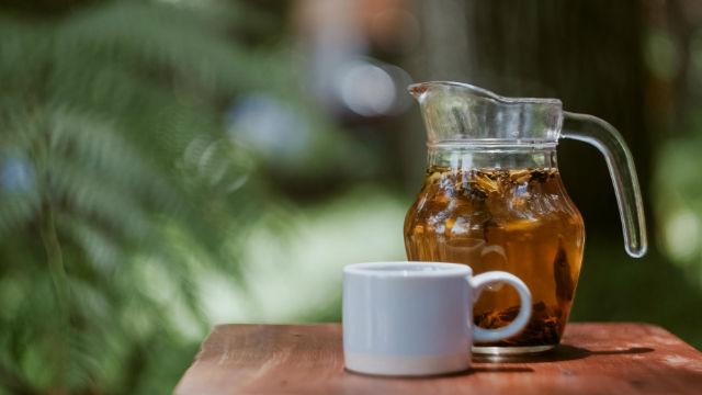 Durchsichtige Kanne mit Tasse Grüner Tee
